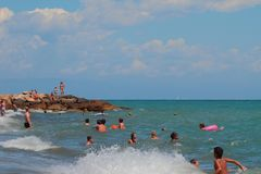 Savona, Italia - 2 luglio 2017: La gente che nuota nel mare difficile Immagini Stock