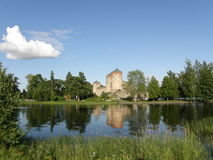 Savonlinna castle and its reflection in the lake. Savonlinna (Olavinlinna, Olofsborg) castle in Finland surrounded by green trees and its reflection in the lake Royalty Free Stock Image