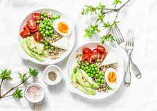 Savory breakfast grain bowl. Balanced buddha bowl with quinoa, egg, avocado, tomato, green pea on light background. Healthy diet royalty free stock photos