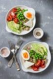 Savory breakfast grain bowl. Balanced buddha bowl with quinoa, egg, avocado, tomato, green pea. Healthy diet food concept. Top vi royalty free stock images