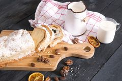 Rustic breakfast with cake and milk. Savory breakfast with sliced pound cake, surrounded by roasted nuts and dried orange, near a bucket of fresh milk, on a Stock Images