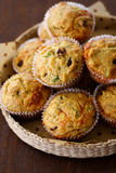 Savory cheese cranberry muffin. Savory muffins with cheddar cheese, dried cranberries and spices arranged on a woven platter on a wooden surface Royalty Free Stock Photography