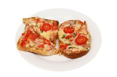 Savory cheese toast. Cheese on toast with ham, tomato and basil on a plate isolated against white Royalty Free Stock Photos