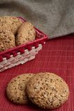 Savory cookies sprinkled with sesame seeds, sunflower on table and burlap background. Savory cookies sprinkled with sesame seeds, sunflower on a wooden table and Stock Photos