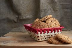Savory cookies sprinkled with sesame seeds, sunflower on table and burlap background. Savory cookies sprinkled with sesame seeds, sunflower on a wooden table and Stock Photo