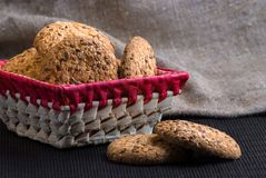Savory cookies sprinkled with sesame seeds, sunflower on table and burlap background. Savory cookies sprinkled with sesame seeds, sunflower on a wooden table and Royalty Free Stock Image
