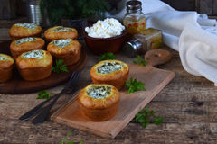 Savory feta cheese muffins with spinach and dill on wooden background. Healthy food concept with copy space for text. Savory feta cheese muffins with spinach Stock Photography