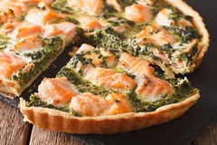 Savory food: sliced tart with salmon, spinach and cream close-up Stock Photos
