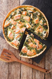 Savory food: sliced tart with salmon, spinach and cream close-up Stock Photography