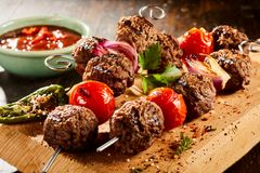 Savory meat balls on skewers with roasted veg Royalty Free Stock Images