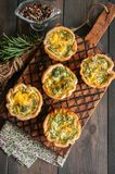 Savory mini quiches tarts on a wooden board. Flaky dough pies. Fresh rosemary and dry thyme on a wooden background Stock Images