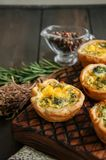 Savory mini quiches tarts on a wooden board. Flaky dough pies. Fresh rosemary and dry thyme on a wooden background Royalty Free Stock Images