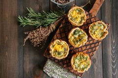 Savory mini quiches tarts on a wooden board. Flaky dough pies. Fresh rosemary and dry thyme on a wooden background Royalty Free Stock Photo