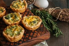Savory mini quiches tarts on a wooden board. Flaky dough pies. Fresh rosemary and dry thyme on a wooden background Royalty Free Stock Image