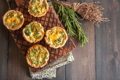 Savory mini quiches tarts on a wooden board. Flaky dough pies. Fresh rosemary and dry thyme on a wooden background royalty free stock photography