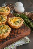 Savory mini quiches tarts on a wooden board. Flaky dough pies. Fresh rosemary and dry thyme on a wooden background Stock Photos