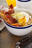 Savory oatmeal porridge with egg and bacon Royalty Free Stock Image