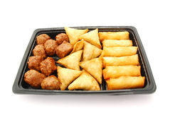 Savory pastry snacks. A black plastic plate with traditional South African savoury party food: delicious curry meatballs, samosas and spring rolls. Image Stock Photos