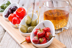 Savory peppers and olives served with whiskey Royalty Free Stock Images