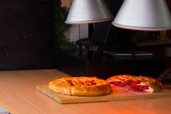 Savory pies keeping warm under heat lamps Stock Images