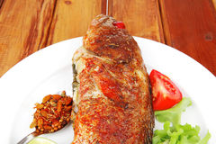 Savory on plate : roast golden fish Royalty Free Stock Images