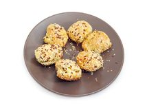 Savory profiterole sprinkled with flax and sesame seeds on dish. Savory profiterole filled with cheese and sprinkled with flax seeds and sesame seeds on the Royalty Free Stock Image