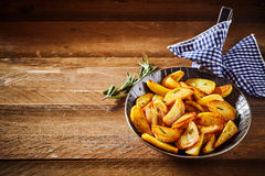 Savory roast potato wedges with rosemary. Savory crispy golden roast potato wedges with fresh rosemary served in an old vintage skillet on rustic wooden boards Royalty Free Stock Photography