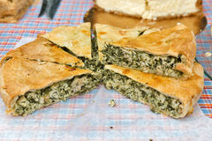 Savory round pie with spinach and meat closeup outdoor. Street food Royalty Free Stock Photo