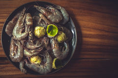 Savory tiger prawns with lime on black plate on wooden table during seafood cooking with copy space and view from above in vintage Royalty Free Stock Images