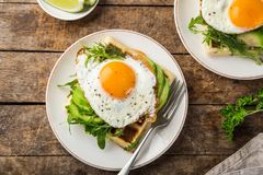 Savory waffles with avocado, arugula and fried egg for breakfast stock photography