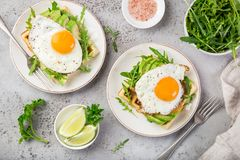 Savory waffles with avocado, arugula and fried egg for breakfast royalty free stock photos
