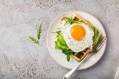 Savory waffles with avocado, arugula and fried egg for breakfast royalty free stock image