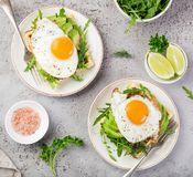 Savory waffles with avocado, arugula and fried egg for breakfast royalty free stock photography