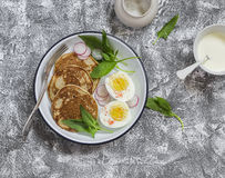 Savory whole grain pancakes, boiled egg and fresh spinach and radishes on the enamel plate on the stone texture. Healthy breakfast or snack Royalty Free Stock Image