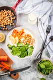 Savory yogurt bowl. Modern vegan food, savory yogurt bowl with beans, chickpeas, spinach, spicy carrots, lemon, Gray stone background, copy space top view Stock Image