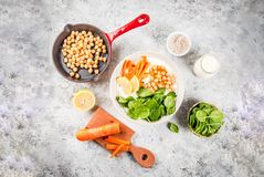 Savory yogurt bowl. Modern vegan food, savory yogurt bowl with beans, chickpeas, spinach, spicy carrots, lemon, Gray stone background, copy space top view Royalty Free Stock Photography