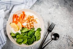 Savory yogurt bowl. Modern vegan food, savory yogurt bowl with beans, chickpeas, spinach, spicy carrots, lemon, Gray stone background, copy space top view Royalty Free Stock Images