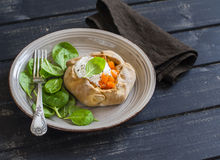 Savoury rustic pumpkin pie and fresh spinach on wood table. Royalty Free Stock Images