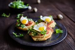 Savoury yoghurt and scallion pancakes with Black Forrest ham, smoked cheese, quail egg and arugula. Savoury yoghurt and scallion pancakes with Black Forrest ham royalty free stock images