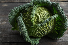 Savoy cabbage on a background of a dark wooden table Stock Photo