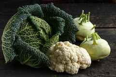 Savoy cabbage, cauliflower and kohlrabion a dark wooden table.  royalty free stock photography