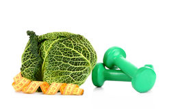 Savoy cabbage, dumbbells and measure tape Royalty Free Stock Images