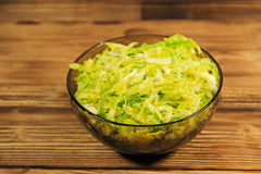 Savoy cabbage salad in glass bowl on wooden table Royalty Free Stock Photo