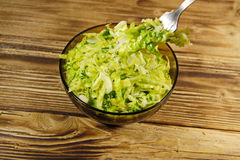 Savoy cabbage salad in glass bowl on wooden table. Fork with salad Royalty Free Stock Image