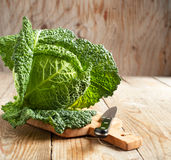 Savoy cabbage on wooden chopping board Stock Photos