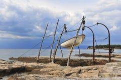 SAVUDRIJA, CROATIA, Jun 26 2013, Small fishing boat hoisted on traditional crane Stock Photography