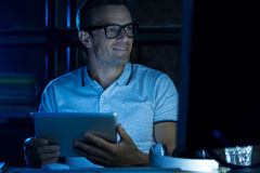 Savvy thoughtful man using many gadgets Stock Photography