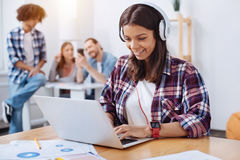 Savvy young woman employing modern technologies for studying. Own private academy. Stunning inspiring pretty lady wearing headphones while watching a video on Royalty Free Stock Photos