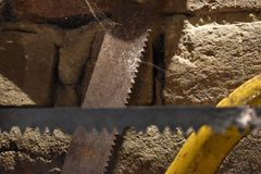 Old saw mill, two saw blades in front of dusty brick wall stock images