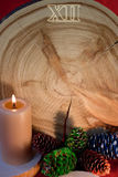Saw cut as Christmas clock, burning candle and painted fir cones Stock Photos
